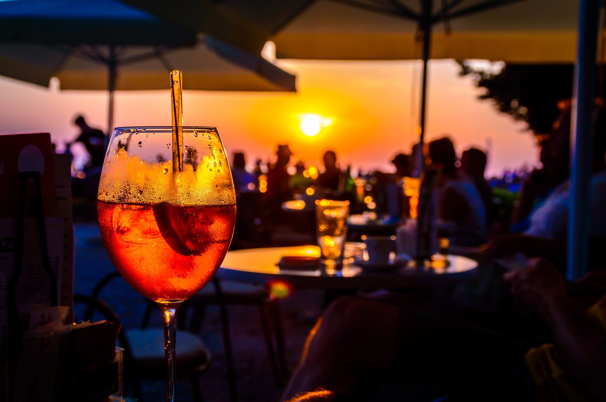 A glass of cold orange cocktail at the sunset on the table of a beach bar at the sunset, with blurry people arround having refreshements or partying on a summer evening, with copy space for text